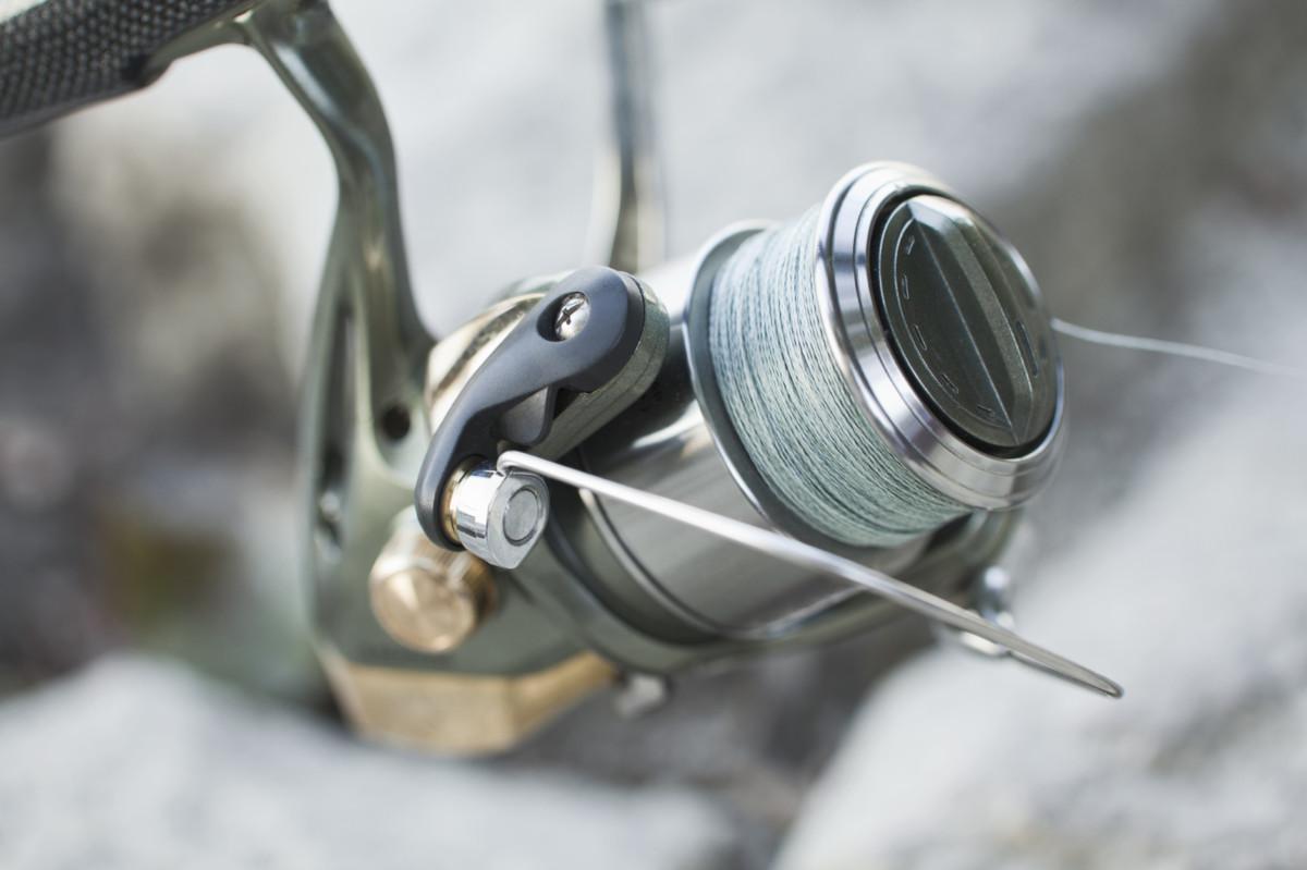 closeup image of alu-body fishing reel atatched onto fishing rod